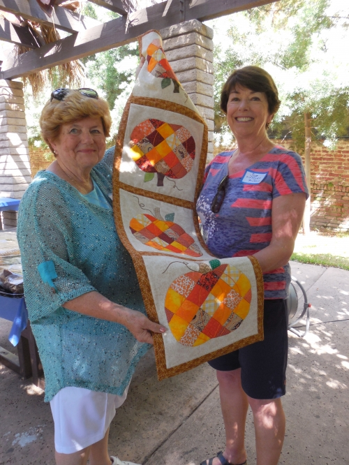 Kathy and Sue holding beautiful hand-quilted table runner. Kathy made it, Sue won it in picnic raffle.